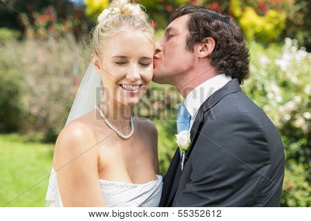 Husband kissing his new wife on the cheek in the countryside