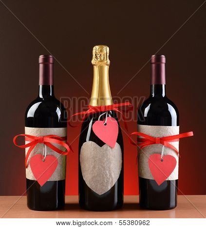 Champagne and wine bottles decorated for Valentines Day. The bottles have red ribbons and heart shaped tags. Vertical format on a light to dark red background.