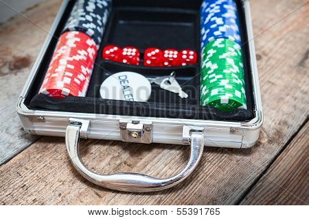 Poker Set In A Metallic Case On Wooden Floor Background