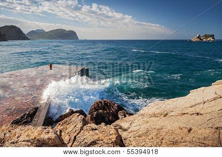 Stone Breakwater With Breaking Waves. Montenegro, Adriatic Sea