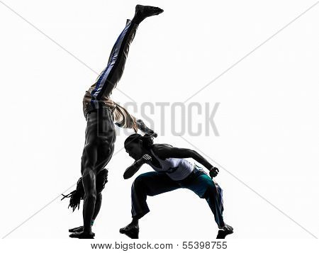 two people couple capoeira dancers dancing in silhouette studio isolated on white background