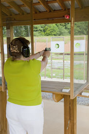 image of shooting-range  - Off duty police officer practicing at the pistol range - JPG