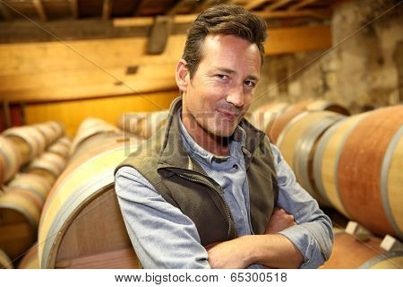 Portrait of winemaker standing in wine cellar