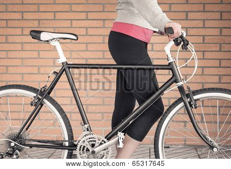 Customized fixie bike and woman over brick wall