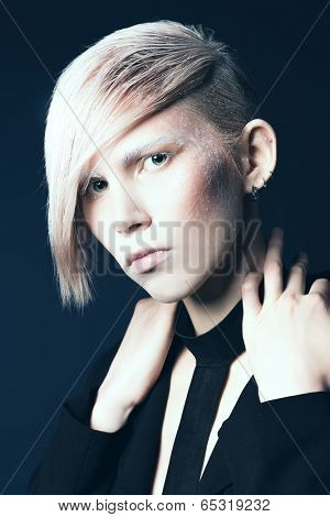 Fashion photo of an extravagant model over black background. Hairstyle, make-up.