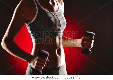 Body of slim female in activewear doing exercise with dumbbells