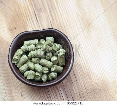beer ingredients: granule of hops on wooden table
