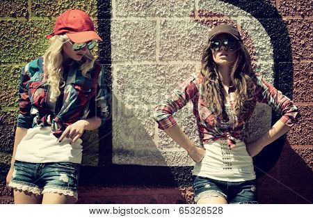 Two teen girl friends together having fun. Outdoors, urban lifestyle. Toned.