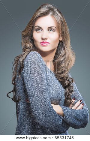 Portrait Of A Beautiful Young Female With Brown Long Hair And Fashion Make Up. Against Gray Backgrou