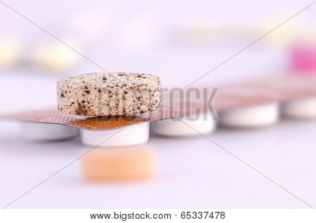 Brown tablet on top of packed medication