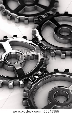 Chrome gear wheels with shallow depth of field over white glossy surface