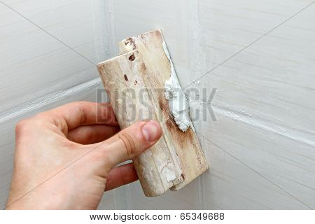 Bathroom Construction - Worker Applying White Grout On Tiles