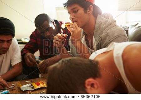 Gang Of Young Men Taking Drugs Indoors