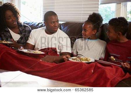 Family With Poor Diet Sitting On Sofa Eating Meal