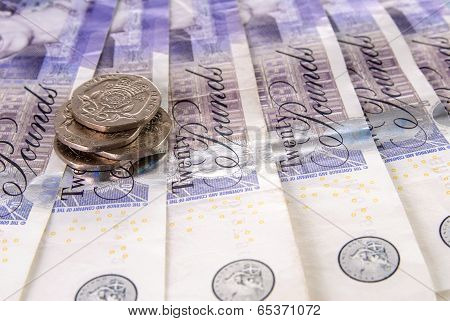Spread Of Twenty British Pound Notes And A Stack Of Coins