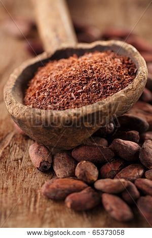 grated dark 100% chocolate  in spoon on roasted cocoa chocolate beans background