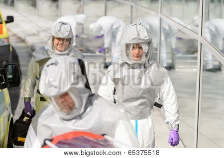 Biohazard medical team in protective uniform walking outside contaminated building