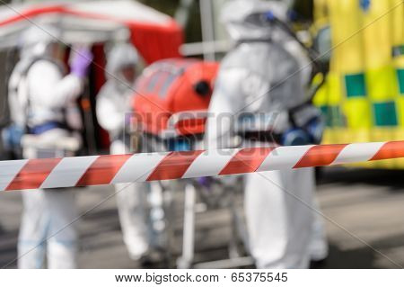 Closeup of crossing barrier tape biohazard medical team in background