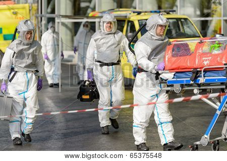Biohazard medical team with stretcher walking on street