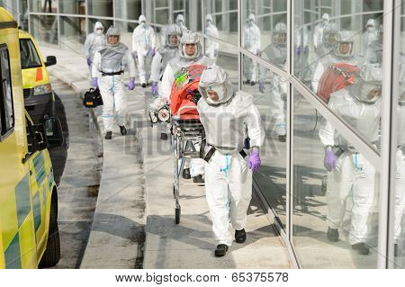 Biohazard team with stretcher wear protective uniform walking outside building