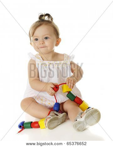 An adorable baby girl happily playing with colorful wooden beads on a string.  On a white background.