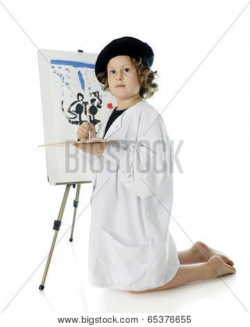 A serious elementary girl kneeling as she paints on an easel in her French beret and white smock.  On a white background.