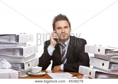 Young Business Man Sitting Self Confident On His Desk, Full Of Paperwork