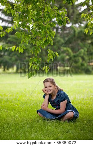 Funny Happy Girl Is Sitting On A Grass