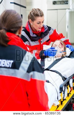 Emergency doctor and nurse or ambulance team transporting accident victim on stretcher