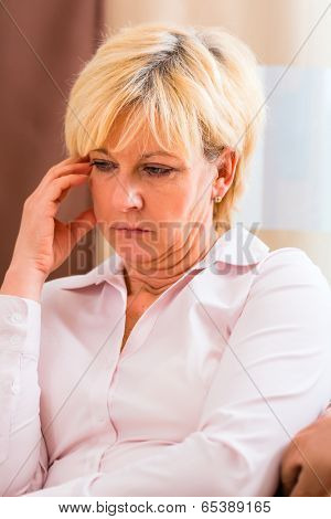 Old woman touching forehead having headache or migraine