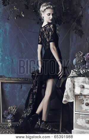 Beautiful slim young woman in a short lace dress posing in a room with vintage blue wall and artistic grunge effect