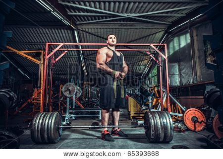 Bodybuilder preparing for deadlift of barbell