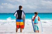 image of boogie board  - Father and son at beach facing ocean with boogie boards - JPG