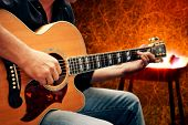 foto of serenade  - man playing guitar against fire background - JPG