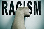 picture of racial discrimination  - a man punching the word racism - JPG