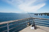 image of sounding-rod  - Recreational fishing gear - rods and reels, tackle box, net,  hooks - on pier. Copy space.