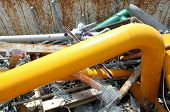 stock photo of ferrous metal  - yellow gas pipe in a landfill of waste of ferrous material - JPG