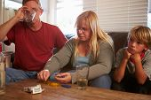 stock photo of meth  - Parents Sit On Sofa With Children Taking Drugs And Drinking - JPG
