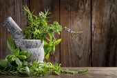 foto of gourmet food  - herbs in mortar on wooden background - JPG