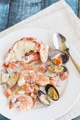 image of cooked blue crab  - Seafood stew made with lobster crab shrimp and clams cooked in coconut milk with tomatoes and onions - JPG