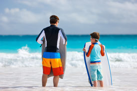 stock photo of boogie board  - Father and son at beach facing ocean with boogie boards - JPG