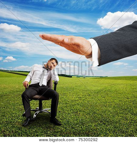 big hand ready to hit lazy businessman on the chair. photo at outdoor
