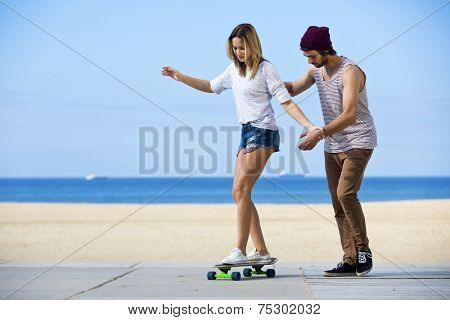 Young man gives his girlfriend her first skateboarding lesson on a seaside boulevard, during a lovely, calm summer afternoon.