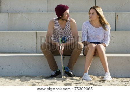 young couple sitting on large concrete steps, engaged in a deep, personal conversation
