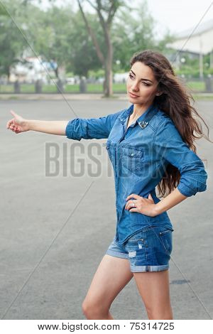 Front View Of A Young Woman Hitchhiking On City Road