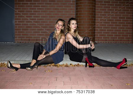 Two Women Sitting On A Curb