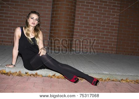 Woman Sitting On A Curb