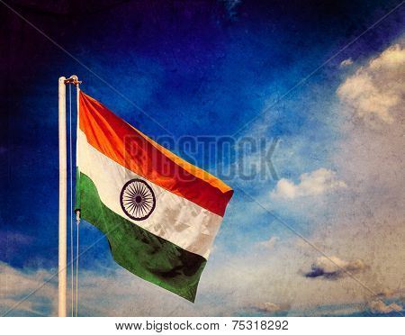 Vintage retro effect filtered hipster style image of  India indian flag in blue sky with copyspace with grunge texture overlaid
