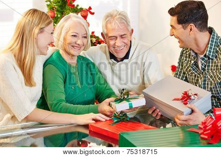 Happy senior citizens celebrating christmas with their children and gifts