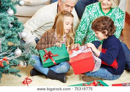 Children celebrating christmas eve with grandparents at home with gifts